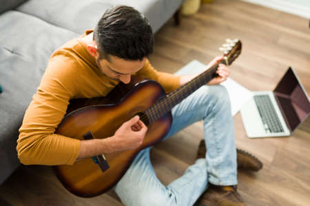 Adult man in his 30s playing the acoustic guitar while sitting on the floor of his home. Latin man watching music videos on his laptop on a leisure day