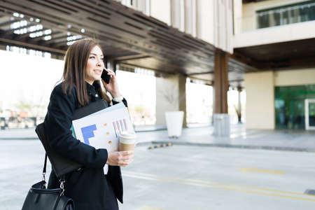 Smart businesswoman multitasking while talking on the phone with a client and carrying work papers. Business woman preparing for a work presentation with print reports and analysis and walking to the office