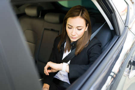 Busy businesswoman looking at the time in her watch and worried about being late to a work appointment with a client. Female entrepreneur on her way to the office on a taxi cab