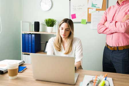 Upset male boss standing next to a female coworker and checking her work. Beautiful caucasian woman working and typing on a laptop at the office desk