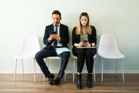 Professional business woman and man looking at their smartphones and texting while waiting for a job interview while sitting in a recruitment office