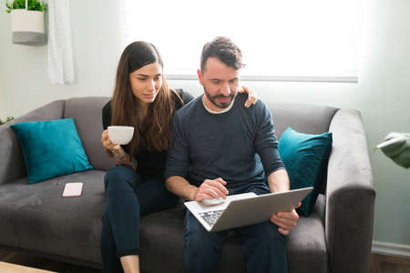 Loving wife hugging her husband while drinking coffee in the morning at home. Hispanic man showing an attractive woman his online shopping on the laptop