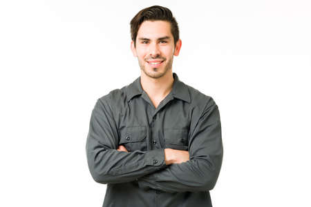 Handsome young man smiling while standing in front of a white background. Hispanic handyman with his arms crossed and making eye contact Imagens