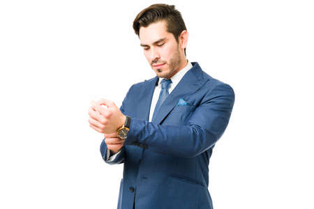 Attractive young man wearing a beautiful suit and putting on his watch. Professional lawyer and businessman getting ready to go to work