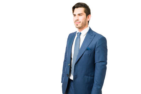 Handsome businessman standing in front of a white background. Thoughtful young man wearing a suit and ready to go to the office