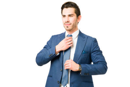 Busy young lawyer putting on and fixing his tie. Successful businessman wearing a suit and feeling proud of his professional work
