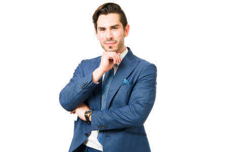 Handsome professional lawyer posing against a white background. Thoughtful businessman thinking and making eye contact with the hand on his chin
