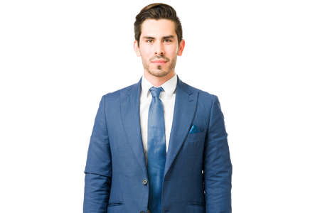Portrait of a good-looking young man wearing a professional suit and making eye contact. Serious hispanic businessman working as a successful lawyer