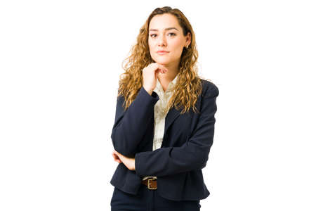Attractive professional woman posing against a white background. Thoughtful young businesswoman making eye contact with her hand on her chin