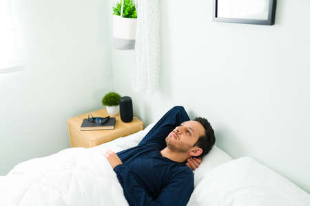 Tired young man with insomnia lying in bed and covered with a white duvet. Hispanic man thinking and feeling stressed while trying to sleep