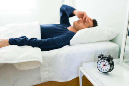 Sleepy young man taking a nap and waking up late with the sound of the alarm. Hispanic man overslept in the morning Banco de Imagens