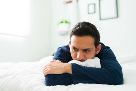 Sad man lying on his stomach in a comfy bed while feeling bad and depressed. Latin man lying in bed hugging the white duvet