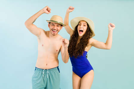 Yes, we did it! Handsome man and beautiful woman wearing swimsuits celebrating and shouting with happiness because they are on vacations Reklamní fotografie