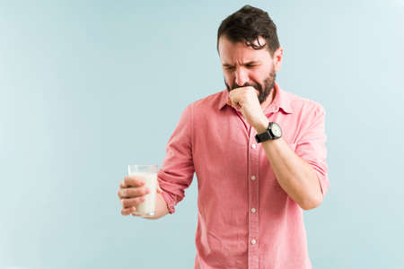Upset man trying to drink a glass of milk and feeling nauseous. Lactose intolerant guy covering her mouth and eating dairy products