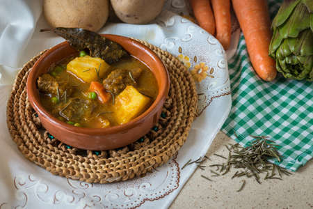 Typical Spanish food, composed mostly of potatoes, peas, carrots, meat, artichoke, etc ...
