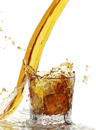 thirsting: yellow liquid splash with glass and ice Stock Photo