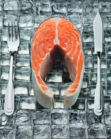 Fresh steak of fish on ice with metal fork and knife photo