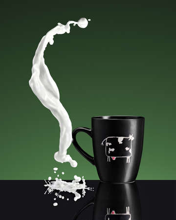 liquid splash of milk near cup with cow on a board liquid splash of milk near cup with cow on a boardn green and black background photo