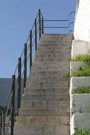 planters: Old stone stairs with a black iron railing and white wall with planters