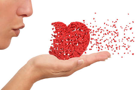 first love: Woman blowing a heart made of little hearts holding on her hand desintegrating on a white isolated background Stock Photo