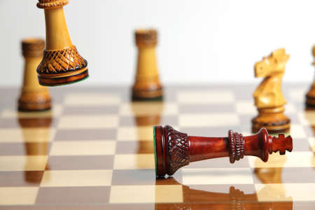 accomplishing: Checkmate with wooden chess pieces on a reflective chessboard Stock Photo