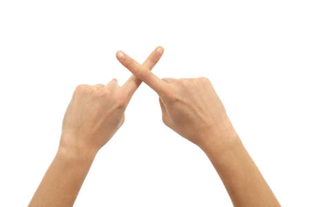 crossing fingers: Woman hands crossing fingers on a white isolated background