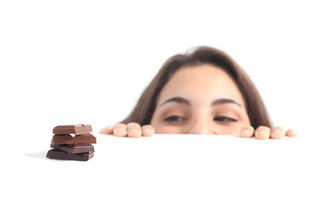 tempted: Beautiful woman tempted by chocolate on a white isolated background