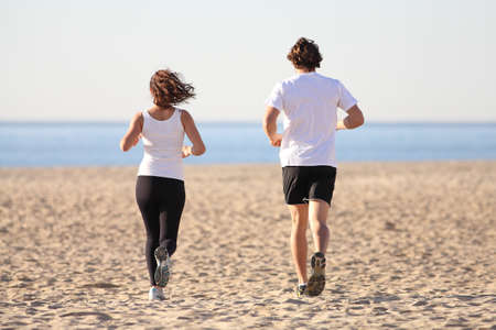 Man and woman running in the beach towards the sea photo