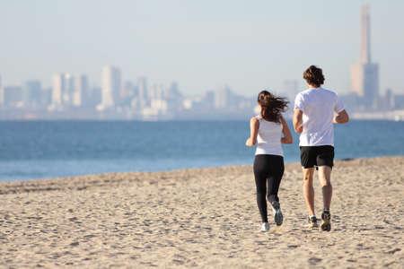 barcelone: L'homme et la femme courant sur la plage vers la mer avec une ville en arri�re-plan