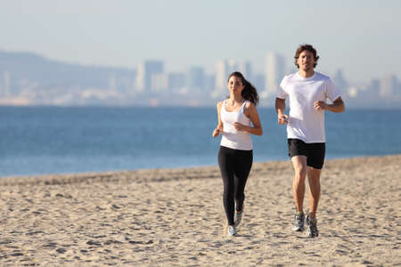 Man and woman running in the beach towards the sea with a city in background                 photo