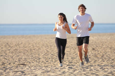 running water: Man and woman running in the beach smiling                 Stock Photo