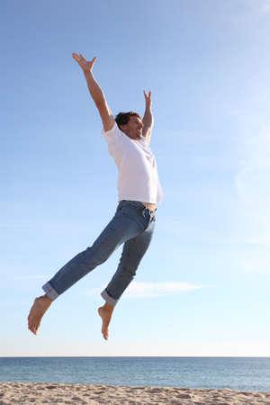 persona saltando: El hombre que salta feliz en la playa con un cielo azul en el fondo