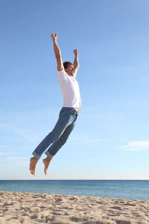 euphoric: Man jumping happy in the beach with a blue sky in the background Stock Photo