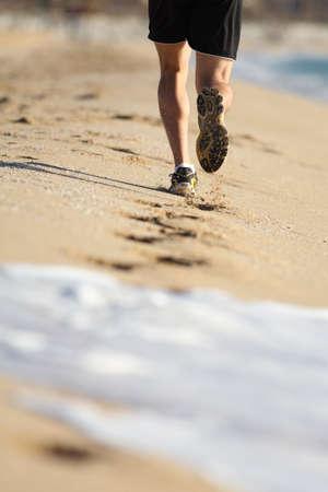 adult footprint: Man legs running on the sand of a beach with water erasing footprints