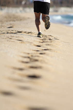 adult footprint: Man muscled legs running on the sand of a beach Stock Photo