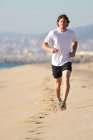 Man running in the beach  Front view Stock Photo