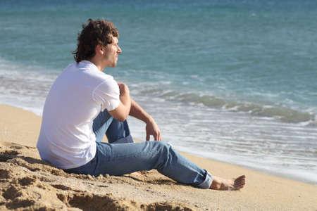Man denken en kijken naar de zee op het strand Stockfoto