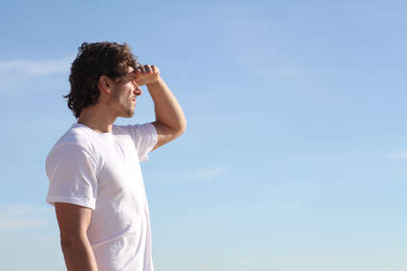 forehead: Man watching the sky with his hand in the forehead Stock Photo