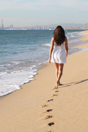 Beautiful woman walking on the beach with her footprints back photo
