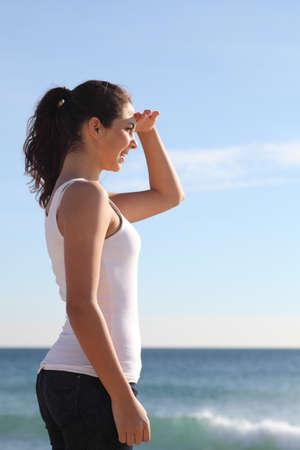 mujer mirando el horizonte: Hermosa niña mirando el mar con una mano en la frente