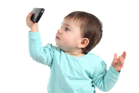 Baby watching concentrated a mobile phone with a white isolated background  Stock Photo