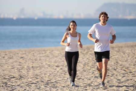 beach front: Man and woman running in the beach towards the sea with a city in background