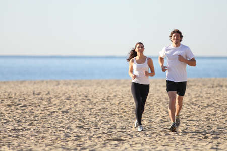 Man and woman running in the beach smiling photo