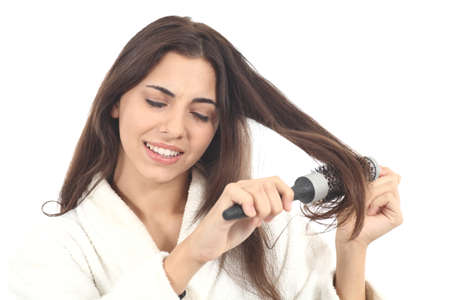 Woman suffering combing with the hairbrush on a white isolated background Stock Photo