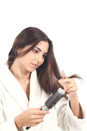 untangle: Beautiful woman with a hairbrush watching her hair on a white isolated background Stock Photo