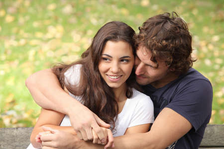 Couple hugging in a park seated in a bench        Banque d'images