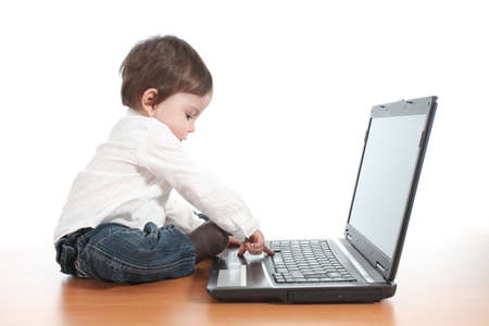easy: Casual baby typing on a laptop computer keyboard with a white isolated background Stock Photo