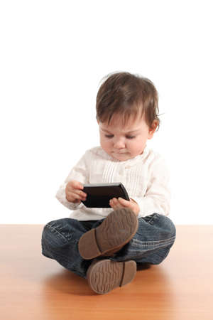 use: Casual baby concentrated in a mobile phone with a white isolated background