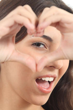 Beautiful woman making a heart shape with her hands on a white isolated background photo
