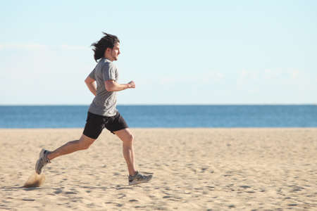 exercise man: Man running on the beach with the sea in the background